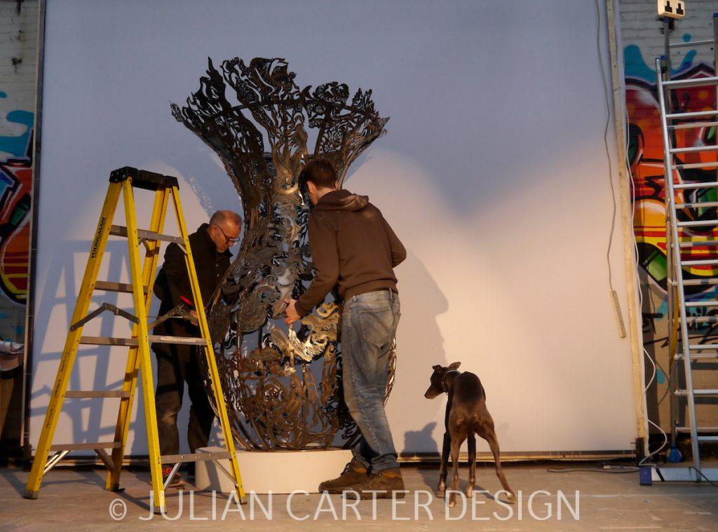 Julian Carter Design. 8 foot steel vase being manoeuvred into position.